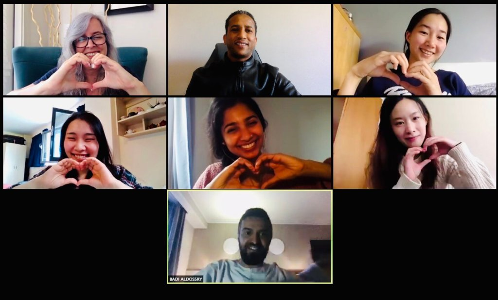 A Zoom screenshot of 7 members of the team, smiling and making heart signs with their hands.